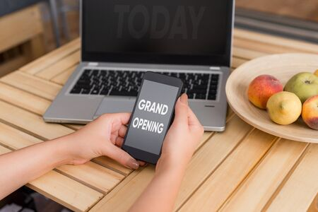 Conceptual hand writing showing Grand Opening. Concept meaning Ribbon Cutting New Business First Official Day Launching woman with laptop smartphone and office supplies technology