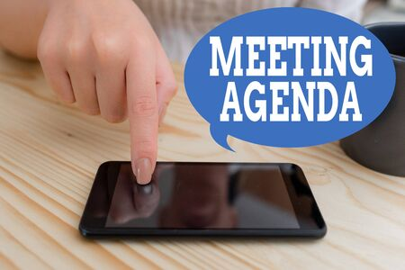 Text sign showing Meeting Agenda. Business photo text items that participants hope to accomplish at a meeting woman using smartphone office supplies technological devices inside home