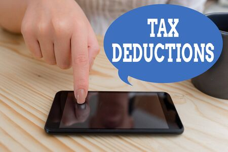 Text sign showing Tax Deductions. Business photo text an amount or cost that subtracted from someone s is income woman using smartphone office supplies technological devices inside home