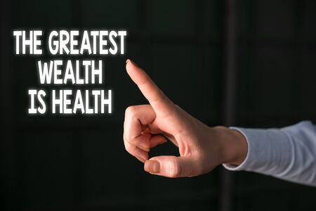 Writing note showing The Greatest Wealth Is Health. Business concept for Many sacrifice their money just to be healthy Finger pointing in the Dark with hand pointing in the copy space