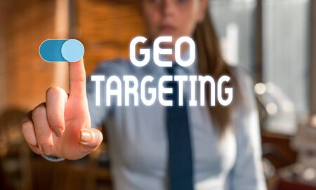 Text sign showing Geo Targeting. Business photo showcasing Digital Ads Views IP Address Adwords Campaigns Location Blurred woman in the background pointing with finger in empty space