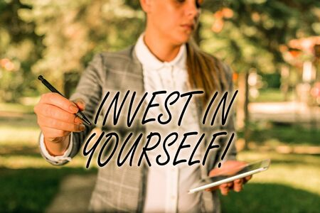 Text sign showing Invest In Yourself. Business photo text learn new things or materials thus making your lot better Outdoor background with business woman holding lap top and pen