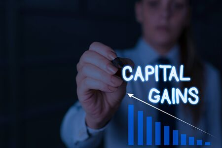 Writing note showing Capital Gains. Business concept for Bonds Shares Stocks Profit Income Tax Investment Funds Woman wear formal work suit presenting presentation using smart device Banco de Imagens
