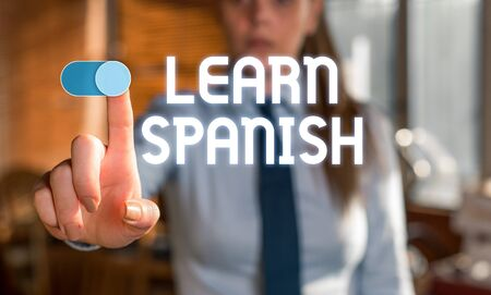 Text sign showing Learn Spanish. Business photo showcasing Translation Language in Spain Vocabulary Dialect Speech Blurred woman in the background pointing with finger in empty space