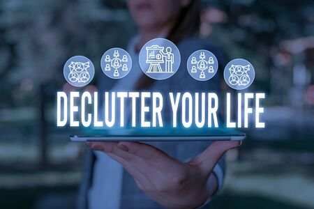 Handwriting text Declutter Your Life. Conceptual photo To eliminate extraneous things or information in life Woman wear formal work suit presenting presentation using smart device