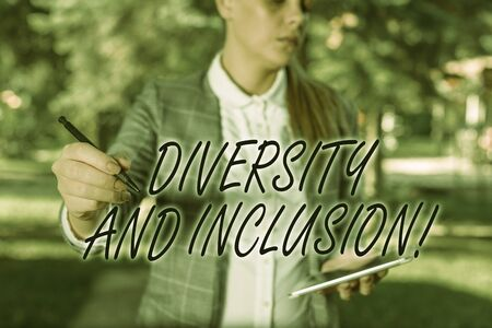 Text sign showing Diversity And Inclusion. Business photo text range huanalysis difference includes race ethnicity gender Outdoor background with business woman holding lap top and pen Stock Photo