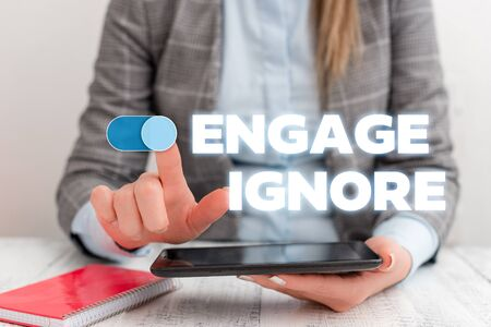 Conceptual hand writing showing Engage Ignore. Concept meaning Silent Treatment Manipulative Punishment Sulking Shunning Business concept with communication mobile phone Фото со стока