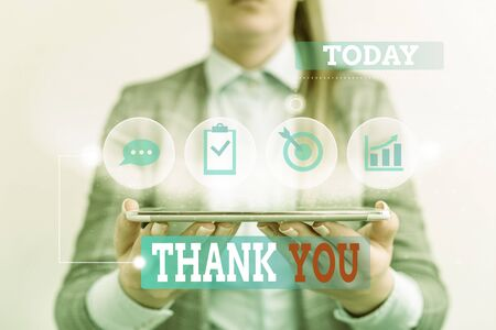 Handwriting text writing Thank You. Conceptual photo a polite expression used when acknowledging a gift or service Female human wear formal work suit presenting presentation use smart device