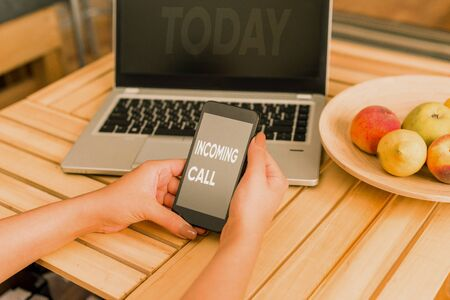 Conceptual hand writing showing Incoming Call. Concept meaning Inbound Received Caller ID Telephone Voicemail Vidcall woman with laptop smartphone and office supplies technology Stock Photo
