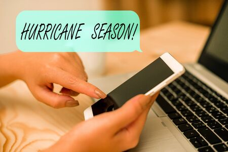 Conceptual hand writing showing Hurricane Season. Concept meaning time when most tropical cyclones are expected to develop woman with laptop smartphone and office supplies technology Stock fotó