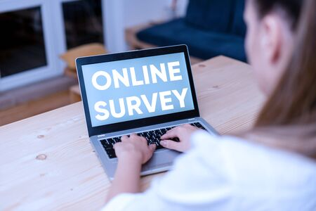 Conceptual hand writing showing Online Survey. Concept meaning Reappraisal Feedback Poll Satisfaction Rate Testimony woman with laptop smartphone and office supplies technology