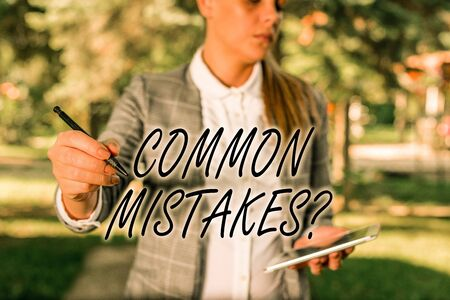 Text sign showing Common Mistakes Question. Business photo text repeat act or judgement misguided making something wrong Outdoor background with business woman holding lap top and pen