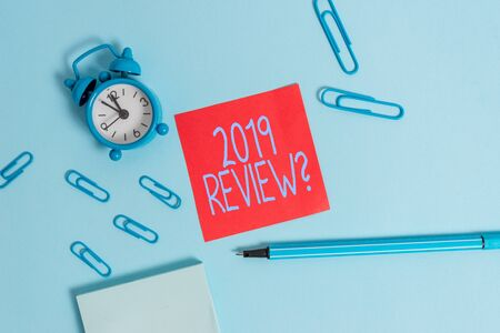 Conceptual hand writing showing 2019 Review Question. Concept meaning remembering past year events main actions or good shows Alarm clock notepad sticky note marker colored background