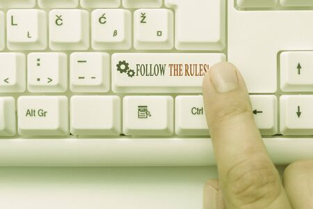 Conceptual hand writing showing Follow The Rules. Concept meaning go with regulations governing conduct or procedure White pc keyboard with note paper above the white background