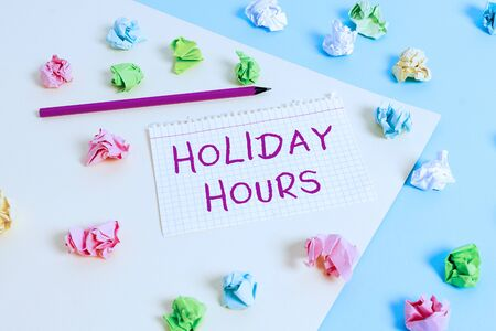 Text sign showing Holiday Hours. Business photo text employee receives twice their normal pay for all hours Colored crumpled papers empty reminder blue yellow background clothespin