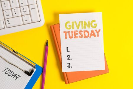 Writing note showing Giving Tuesday. Business concept for international day of charitable giving Hashtag activism Pile of empty papers with copy space on the table