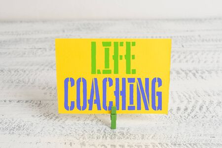 Text sign showing Life Coaching. Business photo showcasing Improve Lives by Challenges Encourages us in our Careers Green clothespin white wood background colored paper reminder office supply