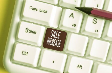 Handwriting text writing Sale Increase. Conceptual photo Average Sales Volume has Grown Boost Income from Leads White pc keyboard with empty note paper above white background key copy space Banco de Imagens