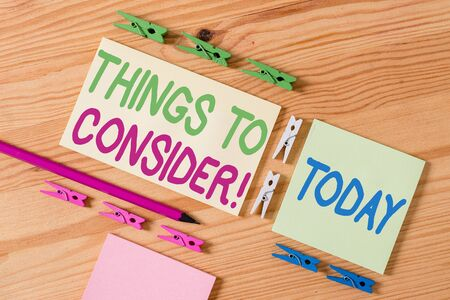 Handwriting text Things To Consider. Conceptual photo think about something carefully in order to make decision Colored clothespin papers empty reminder wooden floor background office Stok Fotoğraf