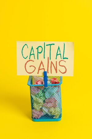 Handwriting text Capital Gains. Conceptual photo Bonds Shares Stocks Profit Income Tax Investment Funds Trash bin crumpled paper clothespin empty reminder office supplies yellow