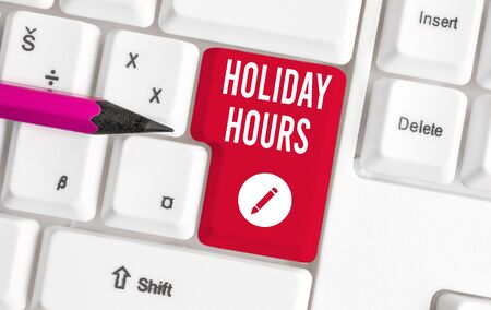 Writing note showing Holiday Hours. Business concept for employee receives twice their normal pay for all hours White pc keyboard with note paper above the white background