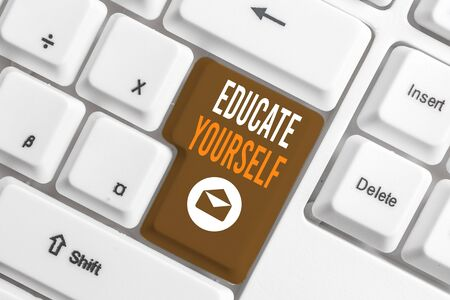 Conceptual hand writing showing Educate Yourself. Concept meaning prepare oneself or someone in a particular area or subject White pc keyboard with note paper above the white background