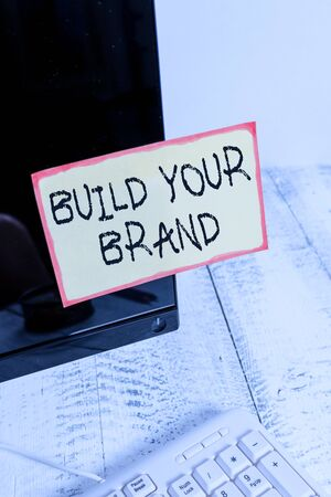 Word writing text Build Your Brand. Business photo showcasing enhancing brand equity using advertising campaigns Notation paper taped to black computer monitor screen near white keyboard Stock Photo