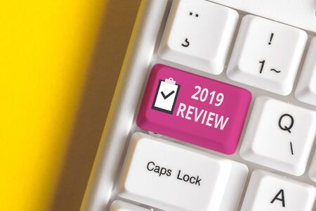 Handwriting text writing 2019 Review. Conceptual photo New trends and prospects in tourism or services for 2019 White pc keyboard with empty note paper above white background key copy space 版權商用圖片