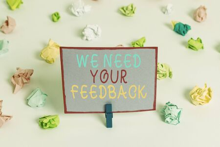 Writing note showing We Need Your Feedback. Business concept for criticism given to say can be done improvement Colored crumpled paper empty reminder white floor clothespin Foto de archivo