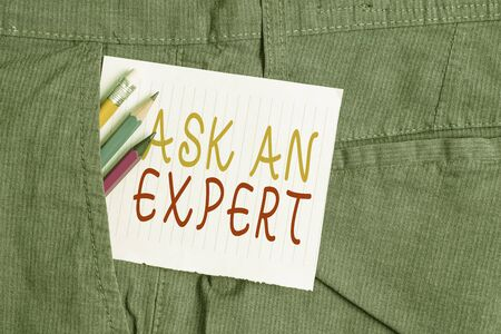 Word writing text Ask An Expert. Business photo showcasing consult someone who has skill about something or knowledgeable Writing equipment and white note paper inside pocket of man work trousers Stockfoto