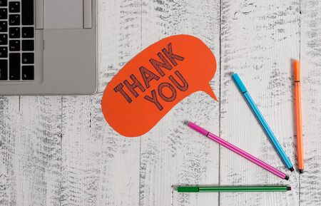 Handwriting text writing Thank You. Conceptual photo a polite expression used when acknowledging a gift or service Open laptop blank speech bubble pens ballpoints lying vintage wooden table