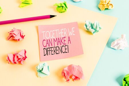 Writing note showing Together We Can Make A Difference. Business concept for be very important some way in like team or group Colored crumpled papers empty reminder blue yellow clothespin
