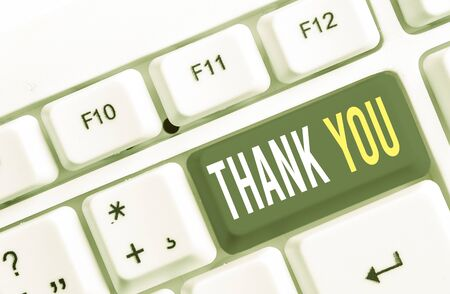 Writing note showing Thank You. Business concept for a polite expression used when acknowledging a gift or service White pc keyboard with note paper above the white background