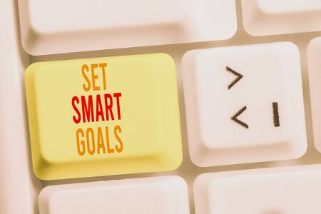 Handwriting text writing Set Smart Goals. Conceptual photo giving criteria to guide in the setting of objectives White pc keyboard with empty note paper above white background key copy space