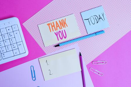 Handwriting text Thank You. Conceptual photo a polite expression used when acknowledging a gift or service Writing equipments and computer stuffs placed above colored plain table