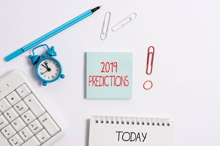 Writing note showing 2019 Predictions. Business concept for statement about what you think will happen in 2019 Copy space on empty note paper with clock and pencil on the table 版權商用圖片