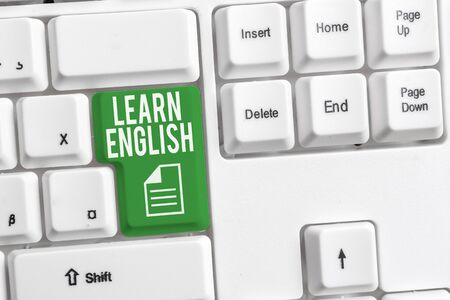 Conceptual hand writing showing Learn English. Concept meaning Universal Language Easy Communication and Understand White pc keyboard with note paper above the white background