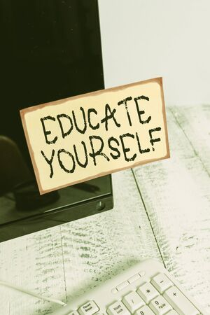 Word writing text Educate Yourself. Business photo showcasing prepare oneself or someone in a particular area or subject Notation paper taped to black computer monitor screen near white keyboard Stock Photo