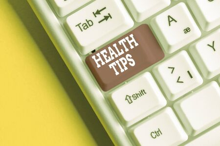Conceptual hand writing showing Health Tips. Concept meaning advice or information given to be helpful in being healthy White pc keyboard with note paper above the white background
