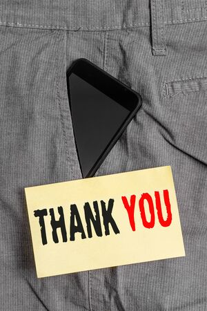 Word writing text Thank You. Business photo showcasing a polite expression used when acknowledging a gift or service Smartphone device inside formal work trousers front pocket near note paper Stok Fotoğraf