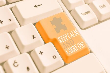 Writing note showing Keep Calm And Carry On. Business concept for slogan calling for persistence face of challenge White pc keyboard with note paper above the white background Stok Fotoğraf - 130371701