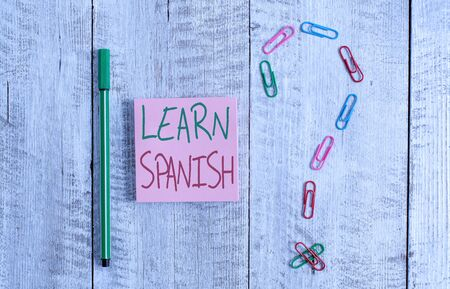 Word writing text Learn Spanish. Business photo showcasing Translation Language in Spain Vocabulary Dialect Speech Pastel colour note paper placed next to stationary above the wooden table