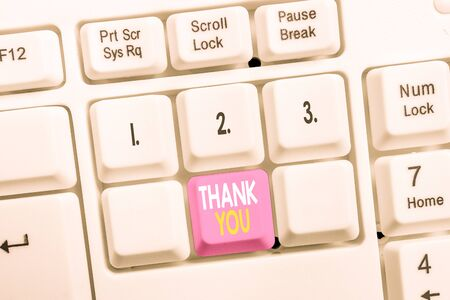 Conceptual hand writing showing Thank You. Concept meaning a polite expression used when acknowledging a gift or service White pc keyboard with note paper above the white background