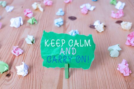 Word writing text Keep Calm And Carry On. Business photo showcasing slogan calling for persistence face of challenge Colored crumpled papers empty reminder wooden floor background clothespin Stok Fotoğraf - 130371546