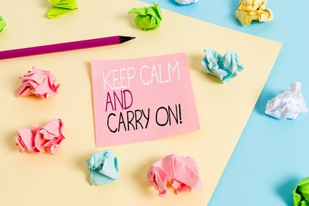 Writing note showing Keep Calm And Carry On. Business concept for slogan calling for persistence face of challenge Colored crumpled papers empty reminder blue yellow clothespin