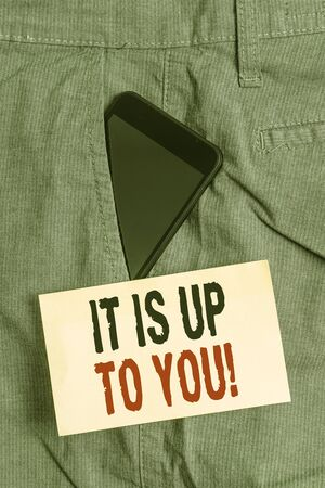 Word writing text It Is Up To You. Business photo showcasing Used to tell a demonstrating that they are the one to decide Smartphone device inside formal work trousers front pocket near note paper Stock Photo