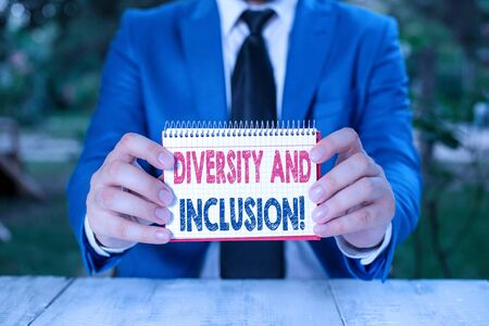 Word writing text Diversity And Inclusion. Business photo showcasing range huanalysis difference includes race ethnicity gender Man holds empty paper with copy space in front of him