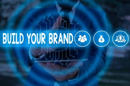 Handwriting text Build Your Brand. Conceptual photo enhancing brand equity using advertising campaigns Male human wear formal work suit presenting presentation using smart device Stok Fotoğraf