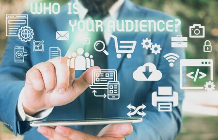 Word writing text Who Is Your Audience Question. Business photo showcasing who is watching or listening to it Male human wear formal work suit presenting presentation using smart device Foto de archivo - 130015465