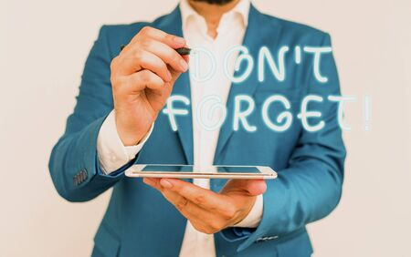 Handwriting text writing Don T Forget. Conceptual photo used to remind someone about important fact or detail Businessman with pointing finger in front of him